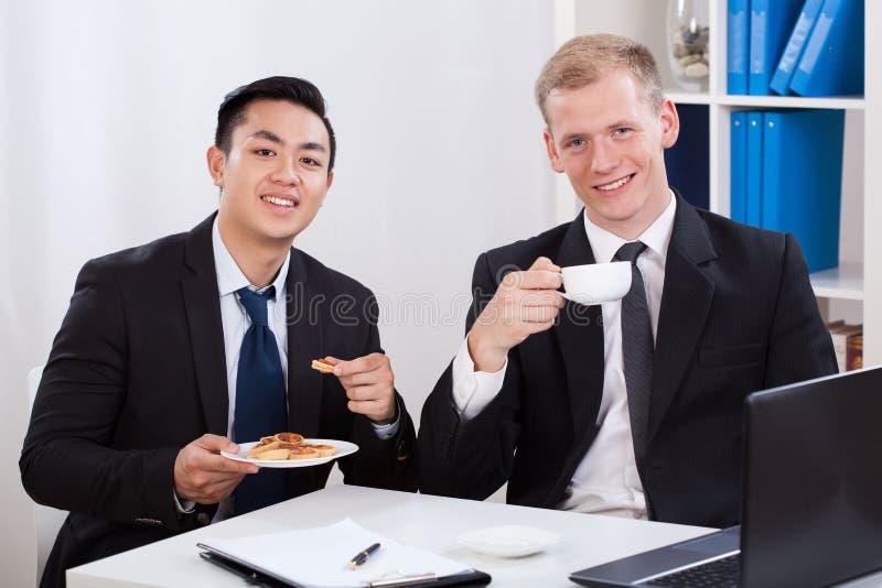 Hommes pendant le déjeuner d'affaires dans le bureau photos libres de droits