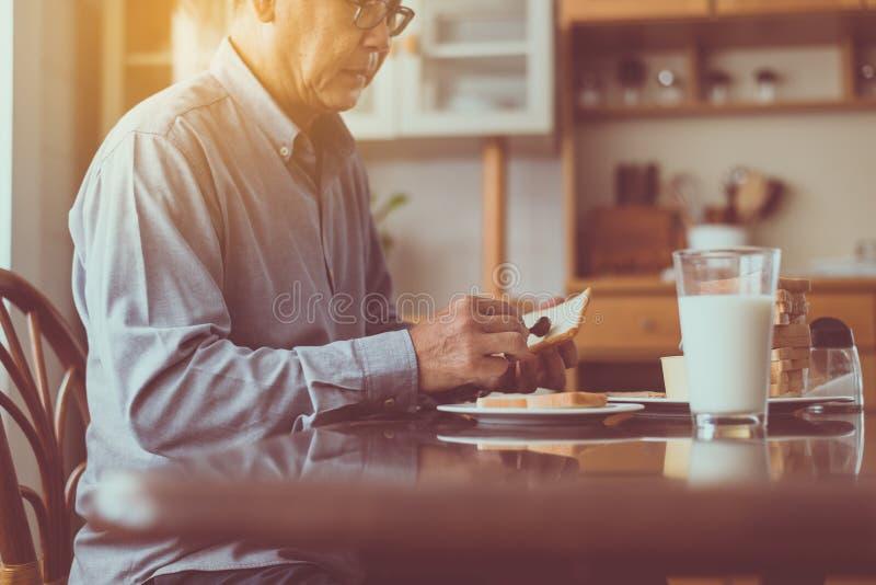 Hommes pluss âgé asiatiques préparant la nourriture saine pour le petit déjeuner avec du pain et le beurre, concept supérieur de  image libre de droits