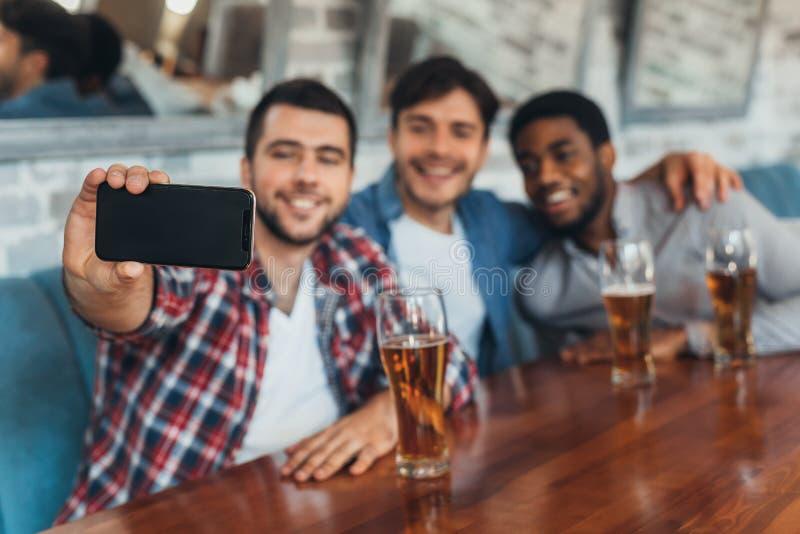 Hommes prenant le selfie et buvant de la bière dans la barre photo libre de droits