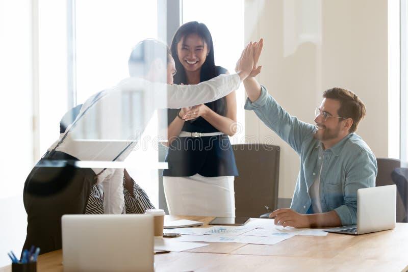 Hommes réussis heureux d'affaires donnant haut cinq lors de la réunion d'équipe photographie stock libre de droits