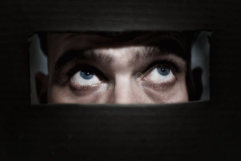 Hommes remarquant par un trou image libre de droits