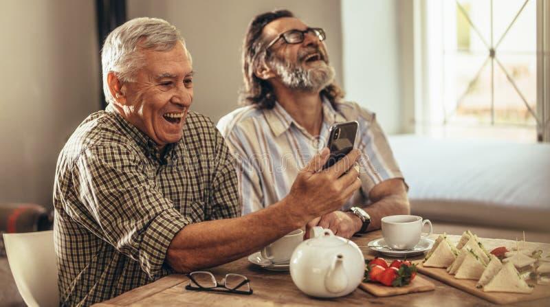 Hommes retirés regardant de vieilles photographies sur le smartphone et le laughin image libre de droits