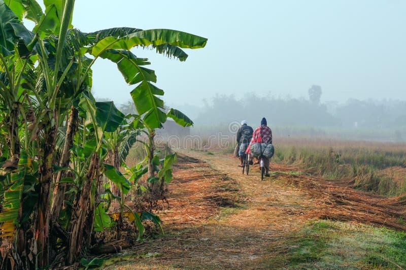 Hommes ruraux indiens faisant un cycle le travail dans le domaine photographie stock