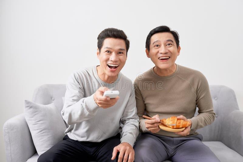 Hommes s'asseyant sur le film de observation de divan à la télévision ensemble à la maison photographie stock libre de droits