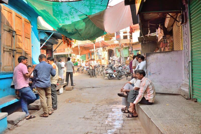 Hommes s'asseyant sur un marché un matin occupé photo libre de droits