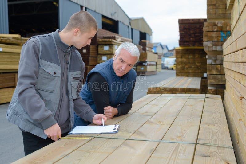 Hommes se penchant sur le presse-papiers de étude en bois de pile photographie stock libre de droits