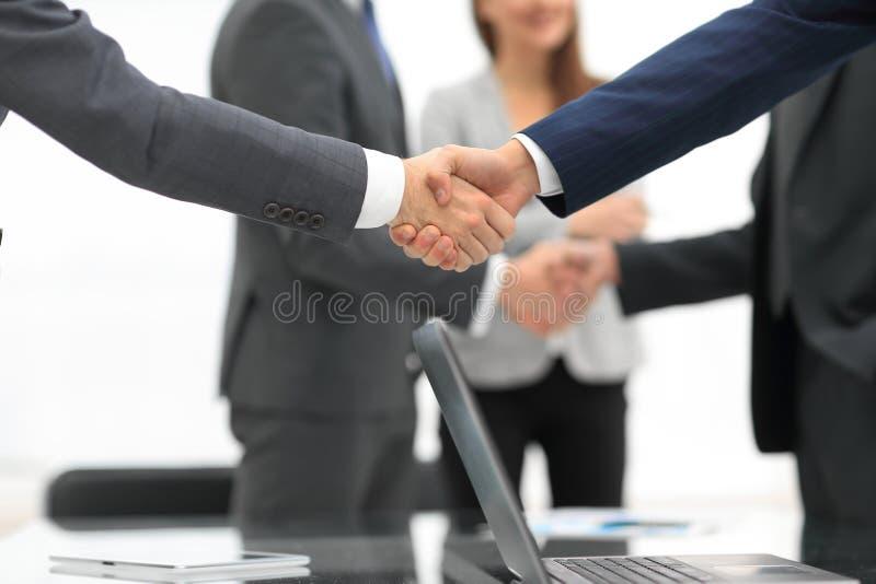 Hommes serrant la main au sourire au bureau avec leurs collègues images stock