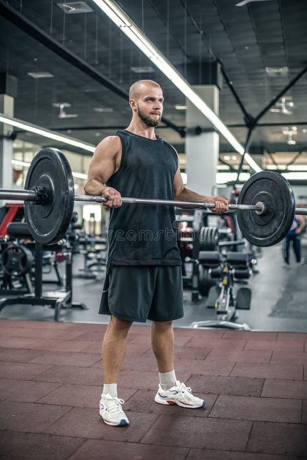 Hommes sportifs chauves forts beaux de forme physique pompant le fond de concept de forme physique de boucle de barbell de séance image stock