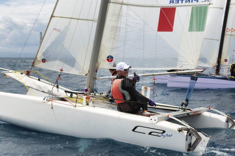 hommes sportifs sur le bateau à voile pendant la régate de catamaran de ressortissant de la formule 18 images libres de droits