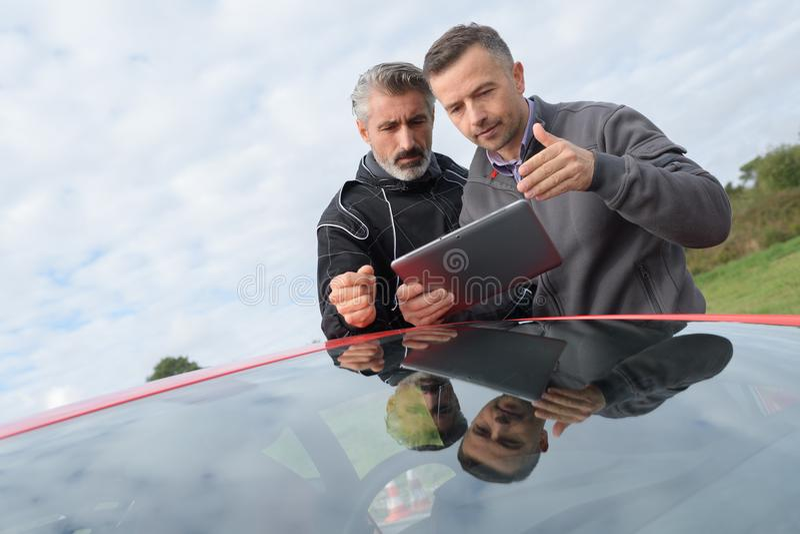 2 hommes sur la promenade en voiture par la campagne avec la voiture de course images stock
