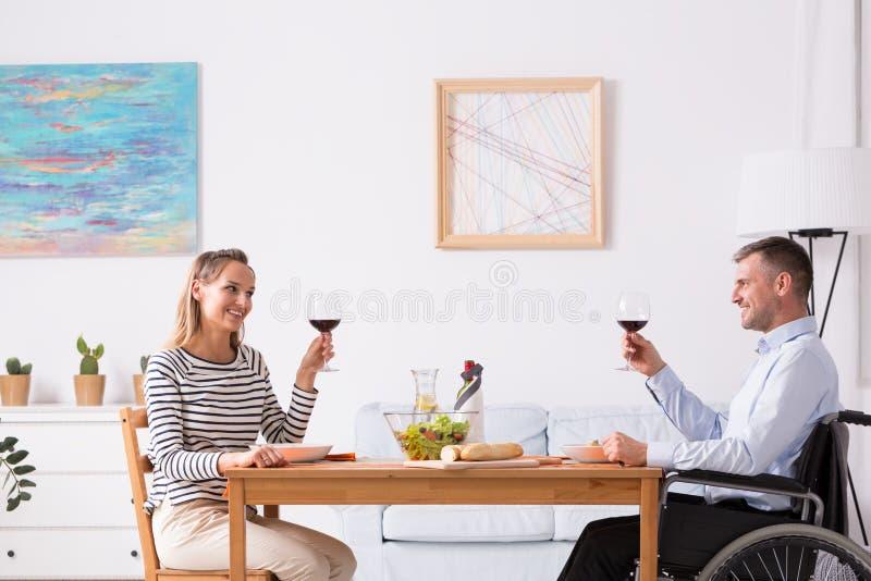 Hommes sur le pain grillé de fauteuil roulant pendant le dîner photographie stock