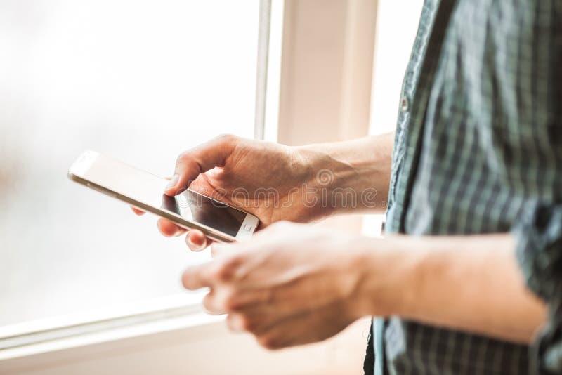 Hommes tenant le tir de plan rapproché de téléphone portable photographie stock