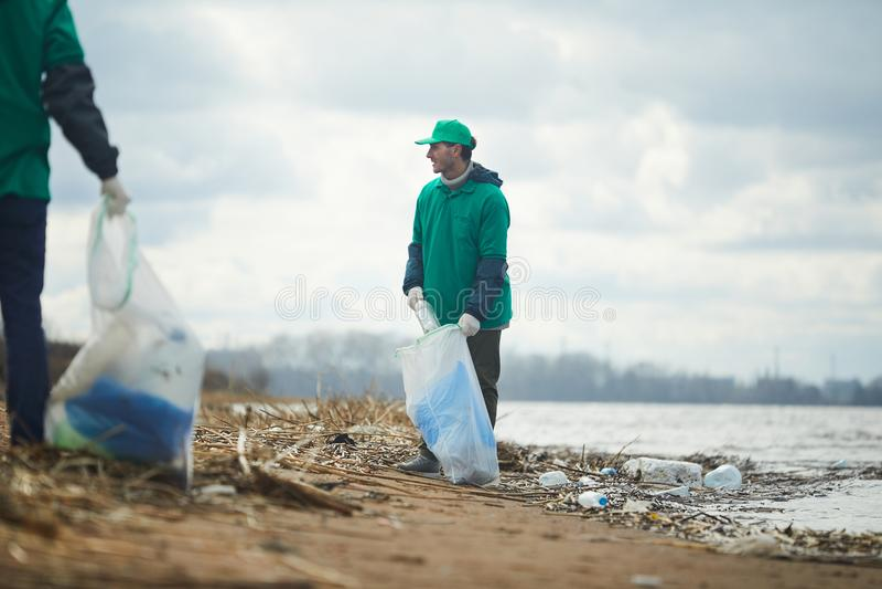 Hommes travaillant et nettoyant le rivage photo stock