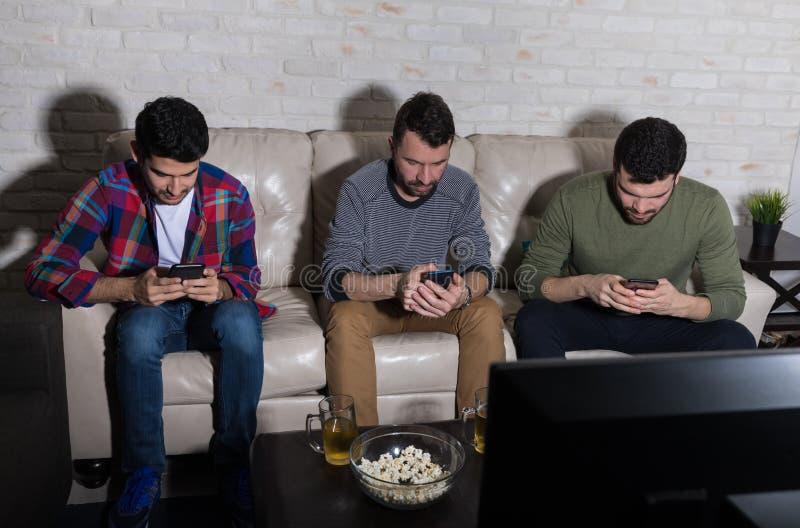 Hommes utilisant des téléphones portables tout en regardant la télévision photo libre de droits