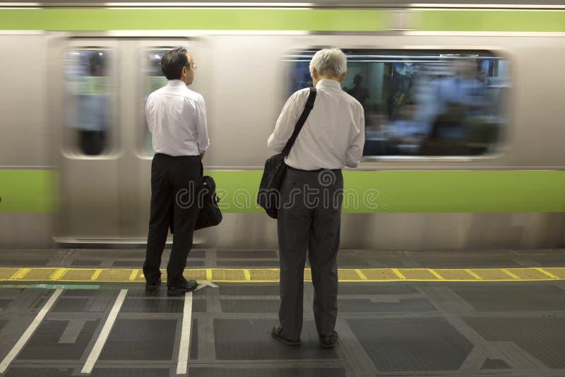 Hommes wainting pour le train au Japon image libre de droits