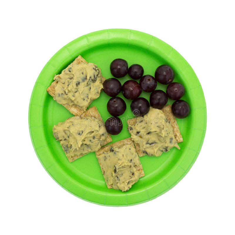 Hommus d'épinards sur les biscuits entiers de grain avec des raisins photos stock