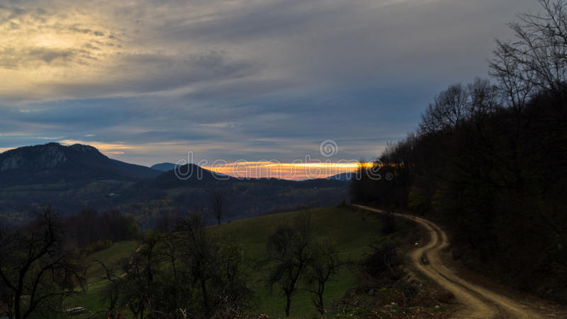 Homolje mountains landscape with a winding gravel country road at sunset of an autumn sunny day stock photos