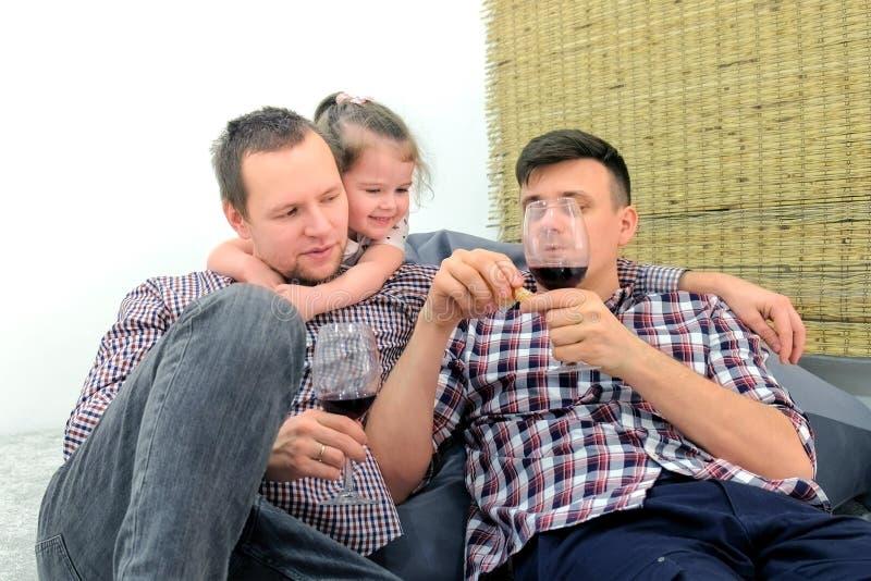 Homoseksualna rodzina z córką je tangerine i napoju wino wpólnie w żywym pokoju zdjęcie stock