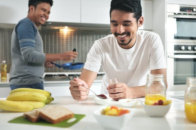 Homoseksualnego pary łasowania Śniadaniowy kucharstwo W kuchni obraz stock