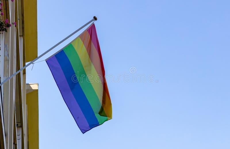Homoseksualnej dumy flagi falowanie przeciw jasnemu niebieskiemu niebu zdjęcie stock
