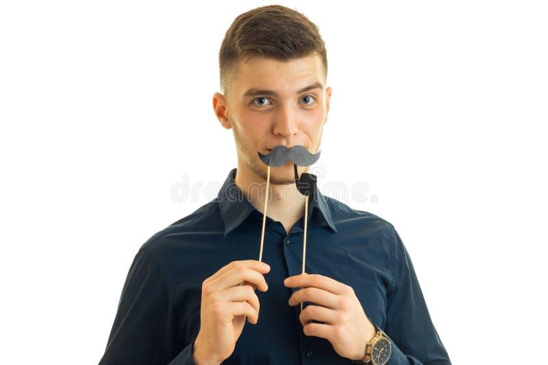 Homoseksualny młody facet Hamming w kamerze z papierowym wąsy zdjęcia stock