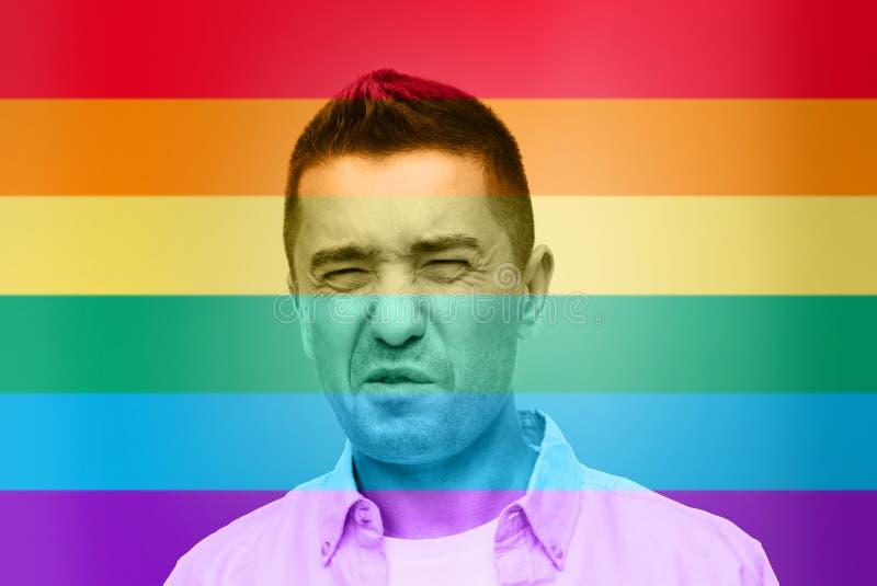 Homoseksueel het wrying over de achtergrond van de regenboogvlag royalty-vrije stock foto