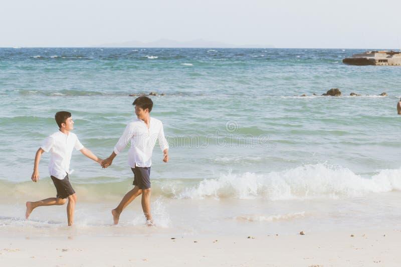 Homoseksueel portret jong Aziatisch paar die met vrolijk samen op strand in de zomer lopen stock foto's
