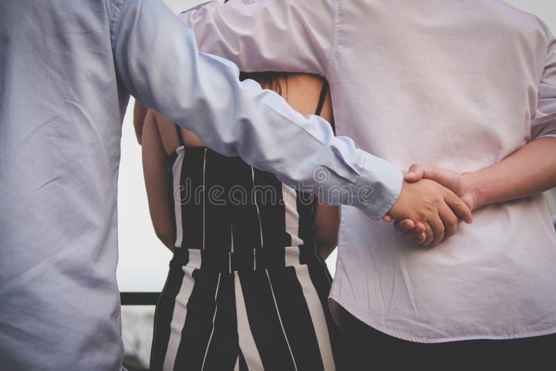 Homoseksuele man omhelzingsvrouw terwijl het houden van handen met geheime minnaar stock fotografie
