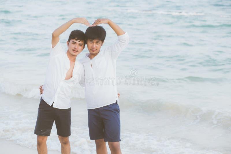 Homoseksuele van het de tribunegebaar van het portret jonge Aziatische paar het hartvorm samen op strand in de zomer stock fotografie