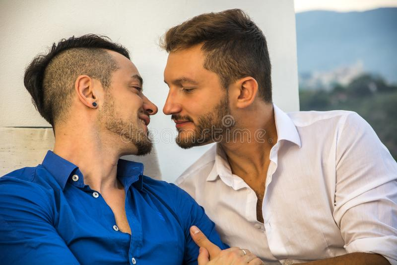 Homosexual couple on chairs at balcony royalty free stock photography