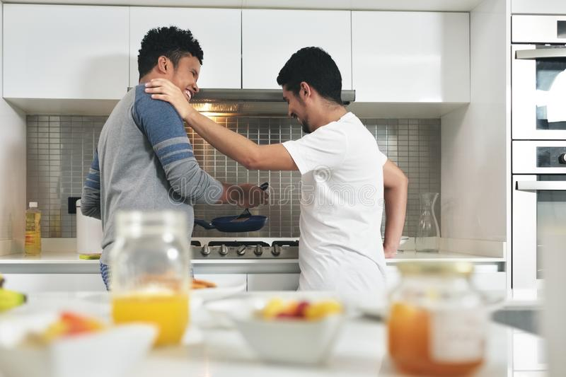 Homosexual Couple Eating Breakfast Cooking In Kitchen. Homosexual couple, gay people, same sex marriage between hispanic men. Happy male partners eating stock photography