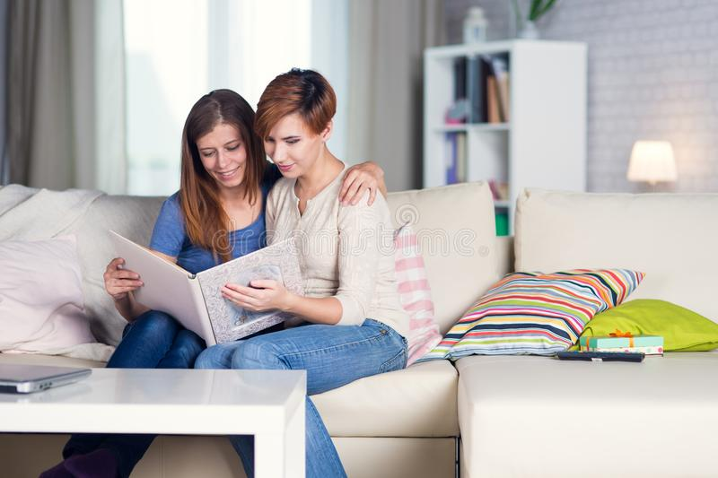 Homosexual couple of lesbian women at home on the couch watching royalty free stock photography