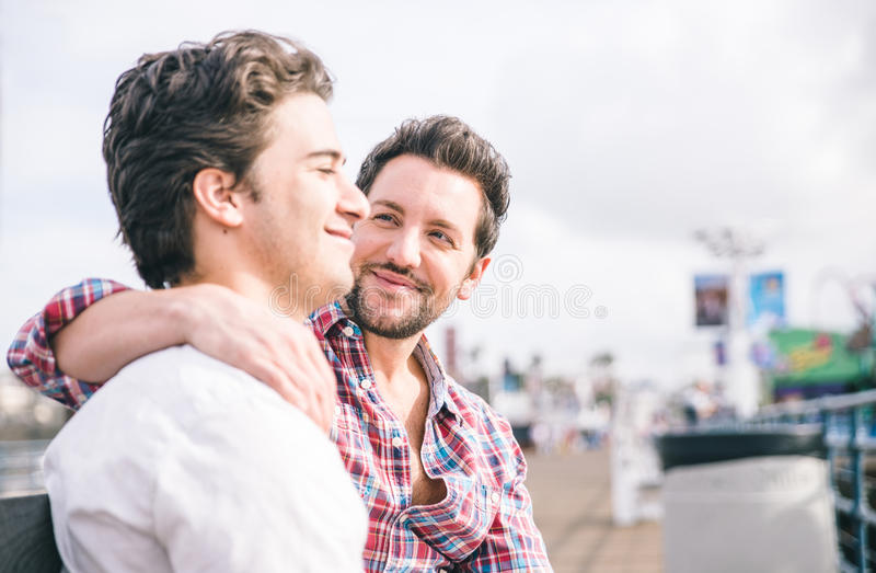 Homosexual couple sitting in Santa monica pier on a bench. Happy gay couple portrait stock photo