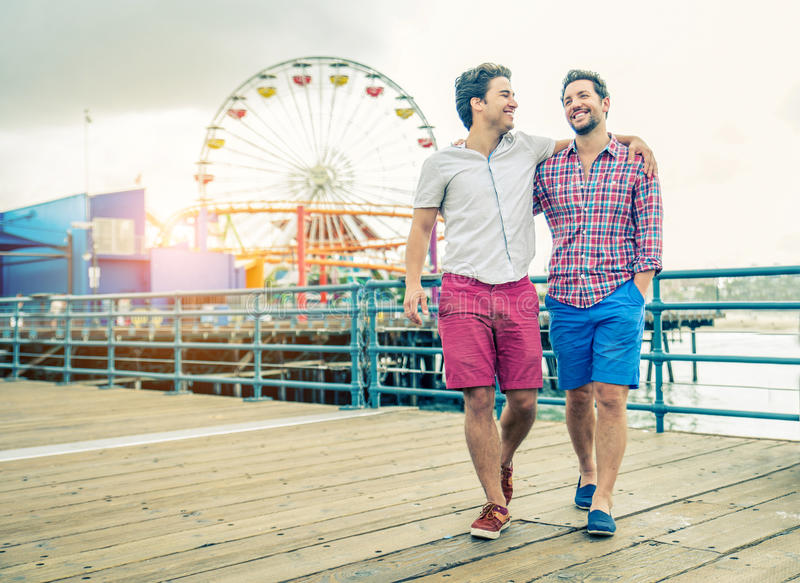 Homosexual couple walking outdoors. Homosexual couple walking on a pier at sunset - Two lovers hugging and having a walk outdoors royalty free stock photography