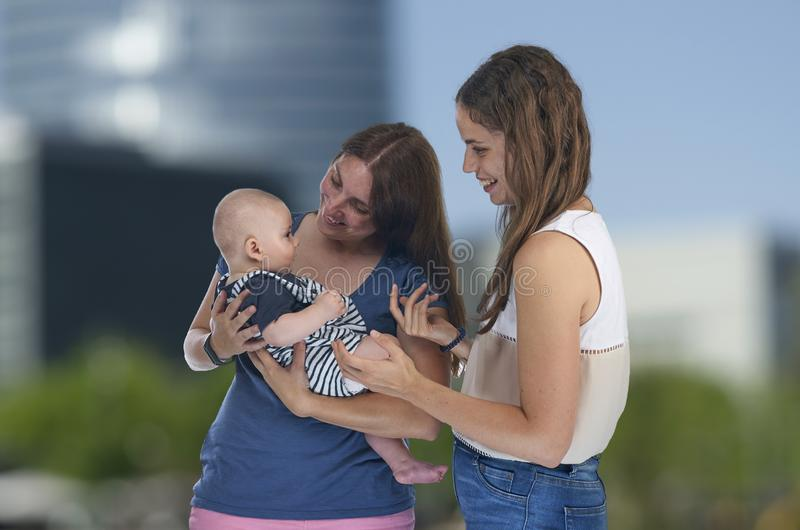 Lesbian love, young lesbian mothers with their baby. Homosexual royalty free stock photography