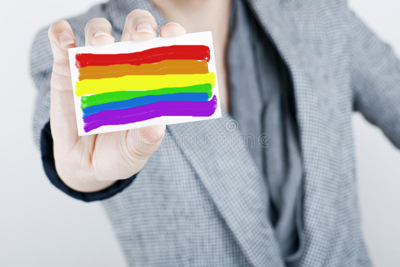 Homosexuals are Welcome. Hand holding and showing rainbow flag business card, homosexuals are accepted in business concept / Equal Opportunity Concept stock photography