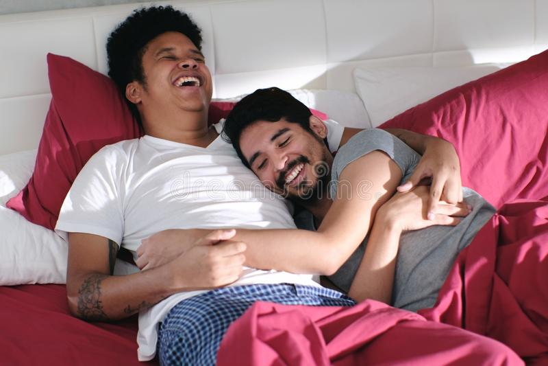 Homosexuella par som kramar och kopplar av i säng arkivbilder