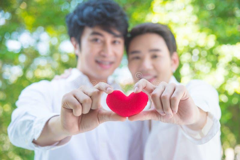 Homosexuella par som tillsammans rymmer hjärtaform och leende för röd färg royaltyfri bild