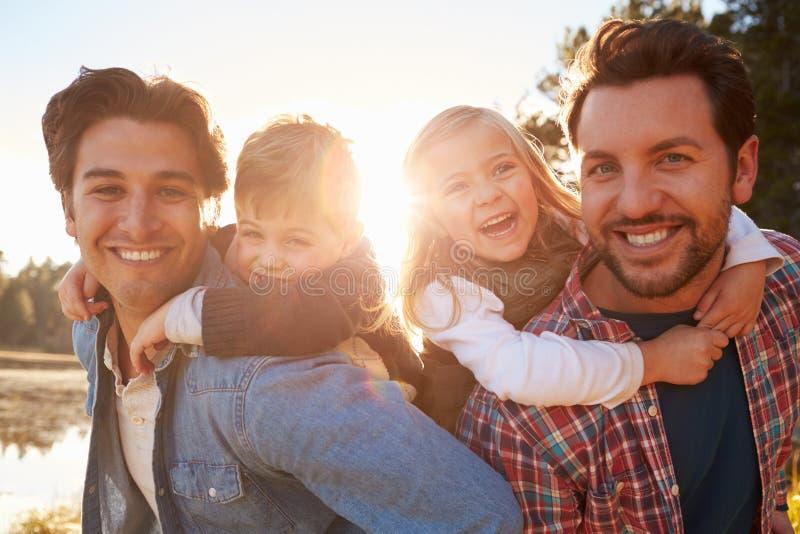 Homosexuelle männliche Paare mit den Kindern, die durch See gehen lizenzfreies stockfoto