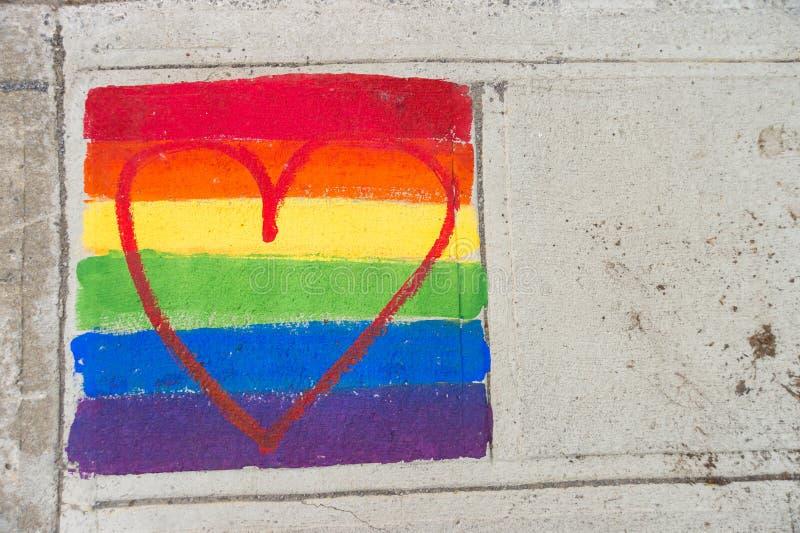 Homosexuelle Regenbogenflagge und rotes Herz lizenzfreie stockbilder