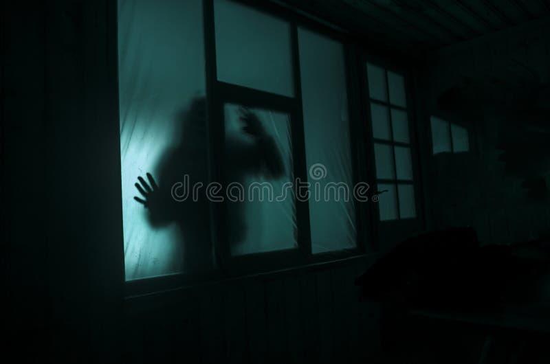 Hon bär en vit ämbetsdräkt Konturn av en människa med besprutade armar framme av ett fönster på natten arkivbilder