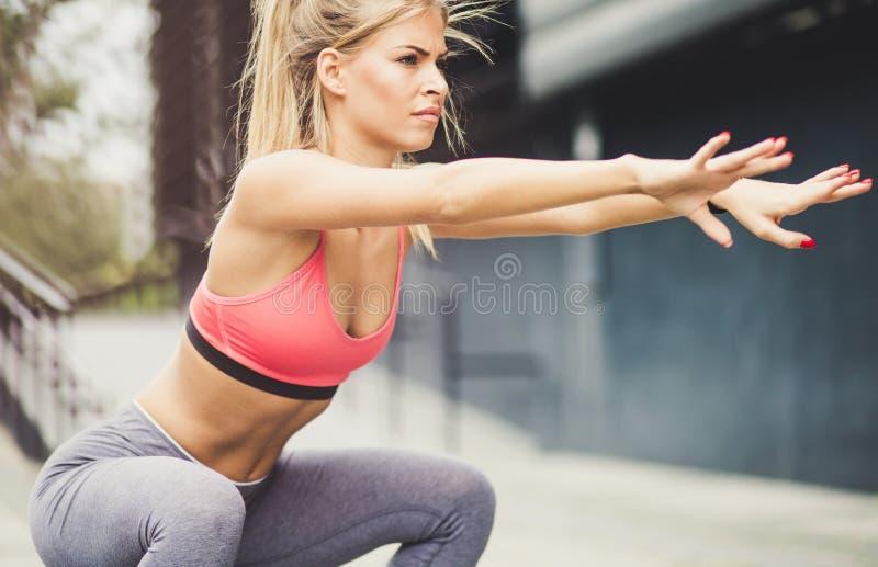Hon squats för att se varm arkivbild