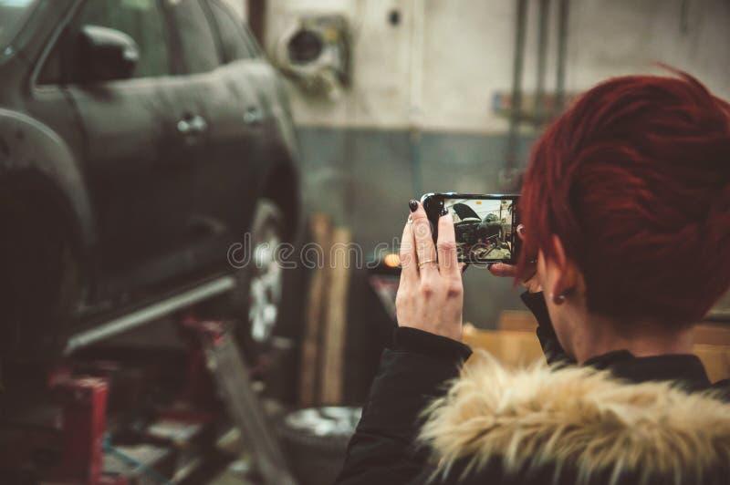 Hon tar ett foto i servicen av den brutna bilen arkivfoton