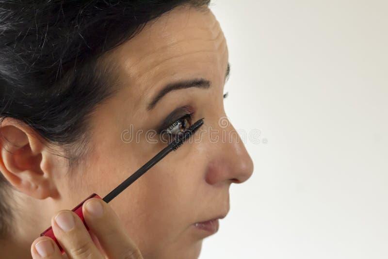 Hon utgör med ögonborstemascara arkivfoton