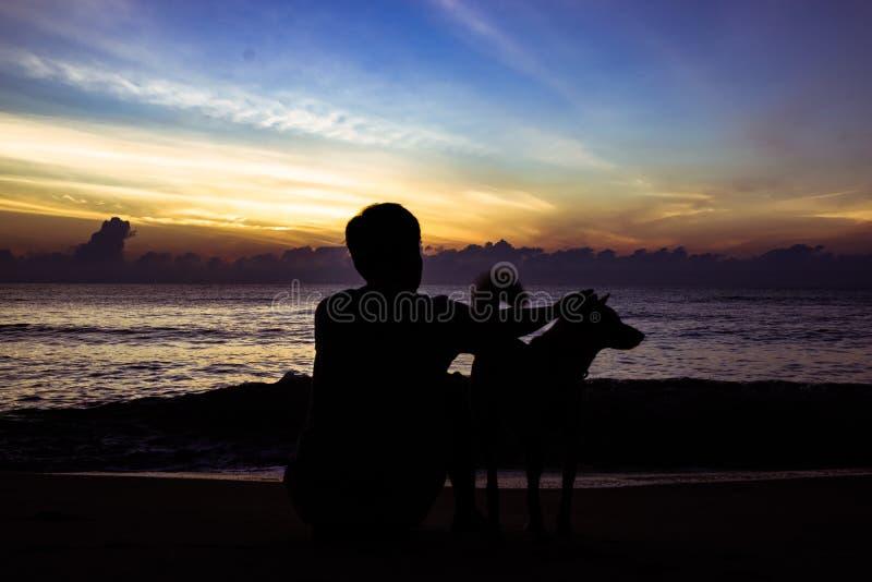 Hond en eigenaar het spelen op het strand met mooie zonlichtachtergrond in de ochtendvakantie stock foto