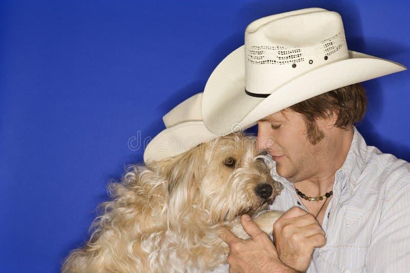 Hond en mens die cowboyhoed dragen stock foto
