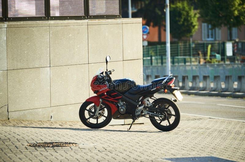 Honda CBR fast motorbike parked in city. STRASBOURG, FRANCE -AUG 5, 2015: Honda 125R CBR motorbike parked in city near a stone wall stock photography