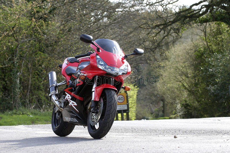 Honda CBR 954 FireBlade static image on a country road. Red and black in early Spring afternoon royalty free stock images
