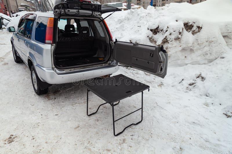 Honda CR-V-erste Generation in der silbernen Farbe mit geöffnetem Stamm und Tabelle für Picknick nahe ihm nachdem dem Säubern vor stockbild