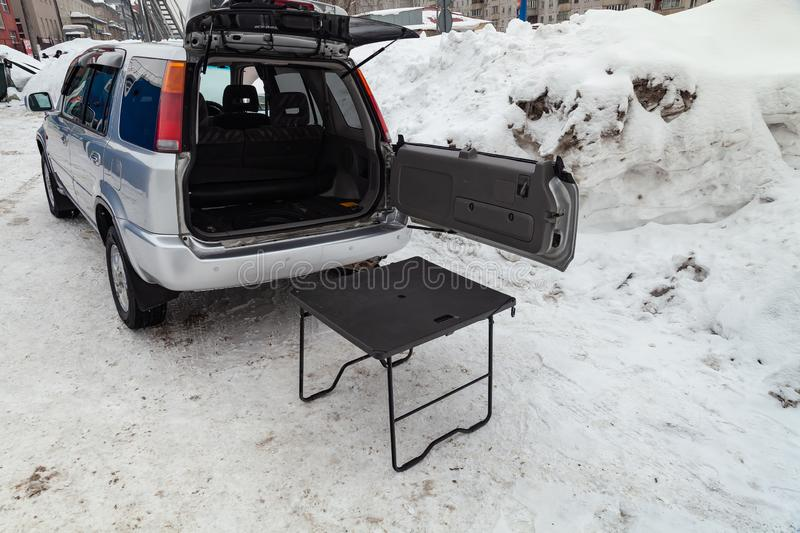 Honda CR-V first generation in silver color with opened trunk and table for picnic near it after cleaning before sale in a winter stock image